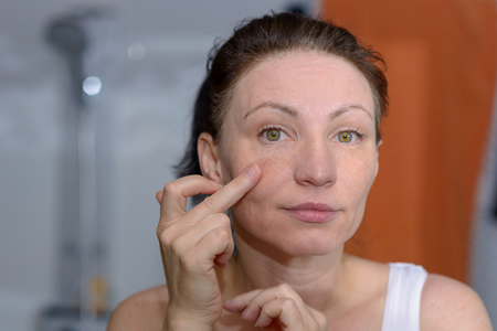 Woman checking her skin in the mirror for signs of ageing and wrinkles pulling on the skin of her cheek