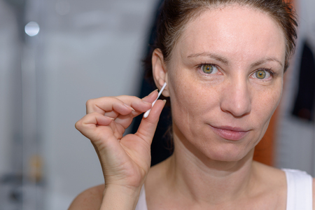 Woman cleaning wax from her ear with a cotton bud as she looks at the camera with a quiet smile in a personal hygiene concept