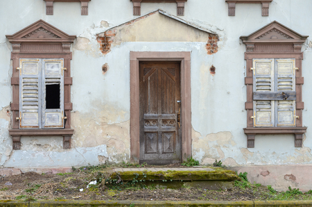 Old house with broken and boarded up shutters and triangular lintels over the wooden door and both flanking windows in a grunge damaged wall