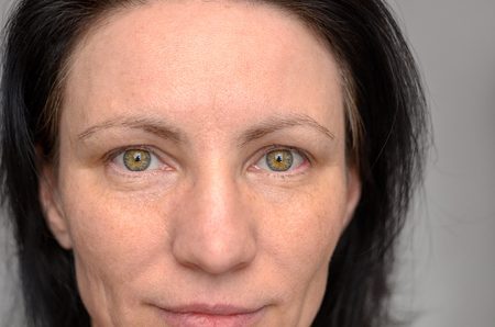 Nose and eyes of a green-eyed woman with dark brown hair staring directly into the lens in a close up cropped view of her face