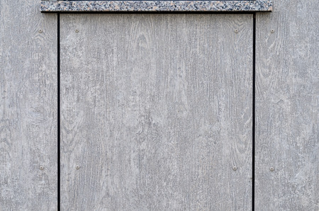 Background texture of two parallel grey wooden boards with wood grain pattern and a crack between them with small nails on either side