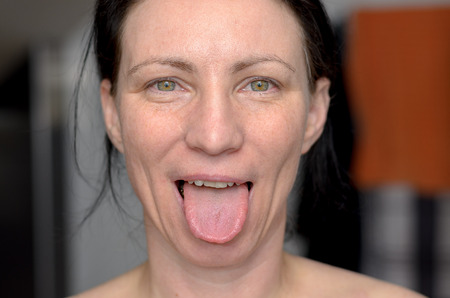 Playful woman with green eyes sticking out her tongue at the camera in a sensual gesture in a close up head shot