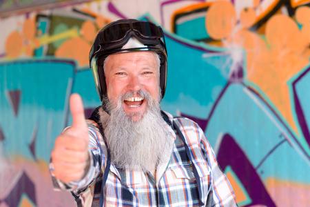 Vrolijke volwassen man met lange grijze baard dragen helm duim opgevend Stockfoto