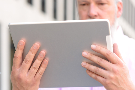 Grey-haired bearded man reading on a handheld tablet computer with a look of concentration in a close up cropped low angle view