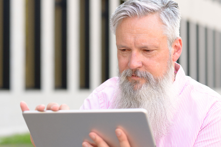 Grey-haired bearded man reading on a handheld tablet computer with a smile in a close up low angle view