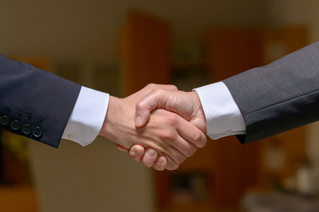 Two businessmen in suits giving a firm handshake gripping each other tightly by the hand over a blurred background