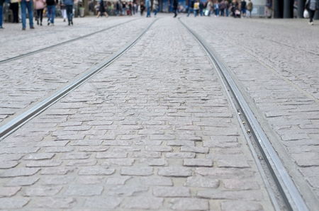 Low angle view of urban tram tracks on a cobbled street receding into the distance with peoples legs visible in the background Stock Photo