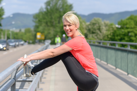 Attractive athletic woman doing warming up exercises using the railing on a pedestrian bridge as she smiles to the camera