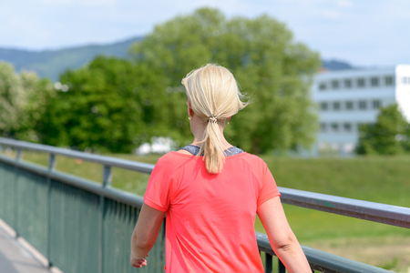 Blond woman striding away across a pedestrian bridge viewed from the rear against greenery and a distant building