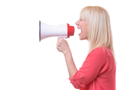 Young blond woman shouting into a megaphone or bull horn isolated on white conceptual of a demonstration or activism Stock Photo