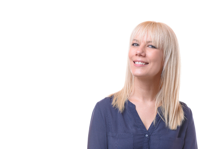 Smiling blond woman with her head turned away glancing sideways back at the camera isolated on white