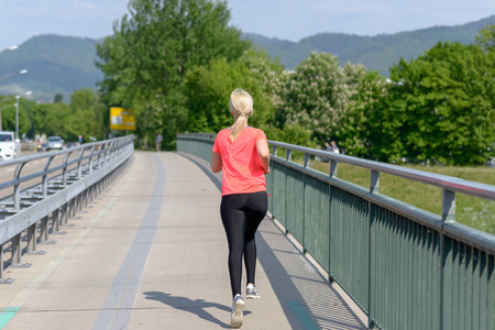 Blond woman jogging away from the camera across a pedestrian bridge in a concept of an active fit healthy outdoor lifestyle