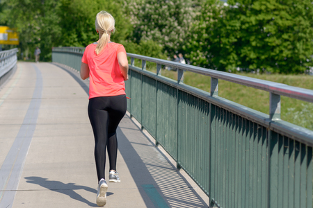 Blond woman jogging away from the camera across a pedestrian bridge in a concept of an active fit healthy outdoor lifestyle, close up Фото со стока