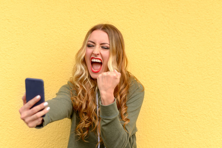 Angry blond woman yelling at her mobile phone and shaking her fist in frustration over yellow Stock Photo