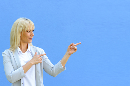 Beautiful young blond woman standing isolated on blue background and pointing at copy space with two hands index fingers, with a smirk on her face Stock Photo