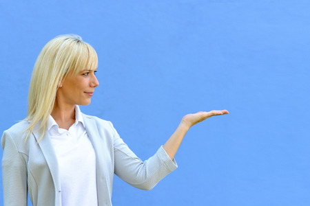 Smiling attractive blond woman holding out her empty hand for product placement over blank copy space over a yellow studio background