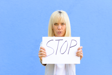 Stern young woman holding up a stop sign handwritten on paper isolated on blue Imagens