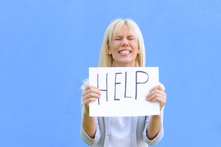 Stressed woman holding up a help sign in her hands as she gnashes her teeth and screws her eyes tight shut over blue Stock Photo
