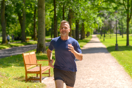 Mann mittleren Alters, der entlang der Gasse im Park am sonnigen Tag in einer Nahaufnahmeansicht joggt