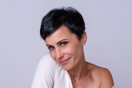 Smiling woman flirting with the camera with one shoulder of her white top pulled down with a charming smile