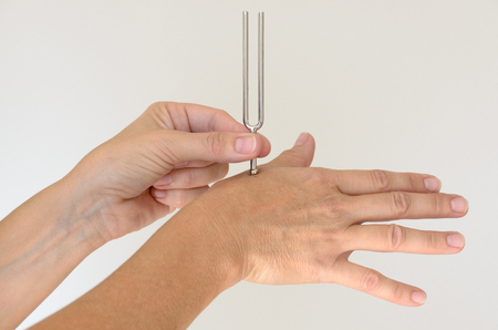 Anonymous person holding metal tuning fork against hand for therapy over white background. Includes copy space. 写真素材