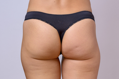 Trim toned buttocks of a slender fit woman wearing g-string black panties in a close up cropped view over grey Stok Fotoğraf