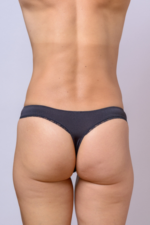 Rear view of a fit slender woman with toned sexy buttocks wearing black g-string panties over a grey studio background