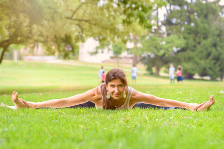 Supple woman working out in an urban park doing the splits while stretching to touch her toes as she looks up at the camera with a friendly smile Stock Photo