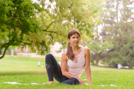 Fit woman sitting in a park on the grass working out doing stretching exercises with her arms raised in a side view with copy space