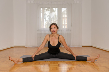 Smiling woman doing splits on mat at home in a health and fitness concept