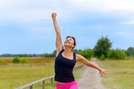 Feliz mujer de mediana edad en forma animando y celebrando mientras camina por un carril rural después de hacer ejercicio trotar en una vista de cerca Foto de archivo
