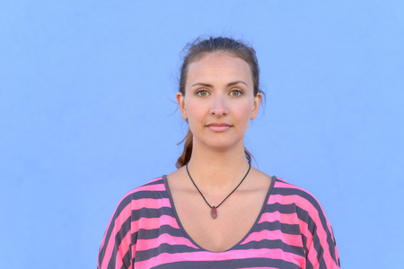 Portrait of beautiful young woman with open eyes, light blue background.