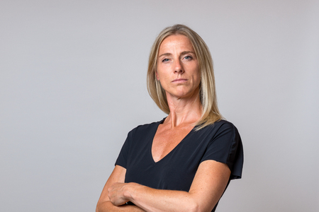 Imperious haughty blond woman with folded arms staring at the camera with a serious intense expression over grey