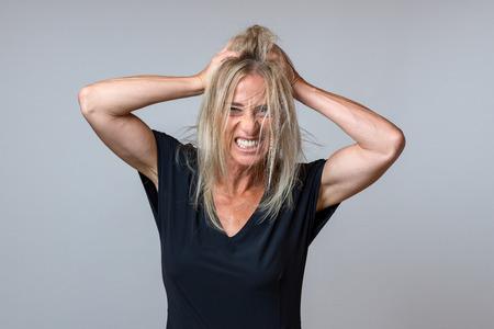 Mujer frustrada rasgando su largo cabello rubio, rechinando los dientes y gruñendo a la cámara sobre gris