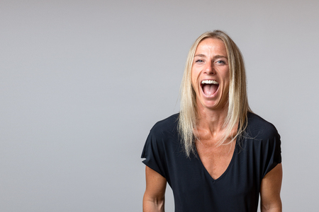 Happy temperamental mature blond woman yelling and glaring at the camera with her mouth wide open isolated on grey with copy space