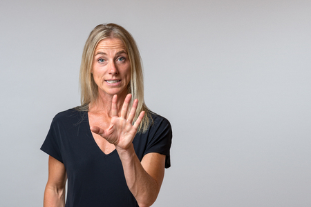 Persuasive vociferous woman speaking and gesturing with her hand in emphasis as she makes a point isolated on grey with copy space