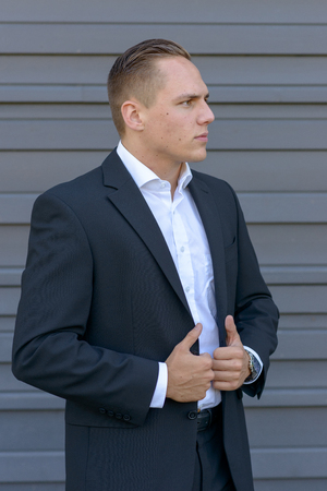 Smart confident young businessman standing waiting looking expectantly off the the right of the frame while gripping his open suit jacket with both hands