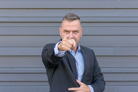 Businessman pointing a finger of blame and accusation at the camera standing against a grey wall, focus to face