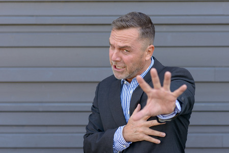 Businessman making a halt gesture with one hand, covering his chest with the other, as though trying to fend off someone against a grey wall with copy space