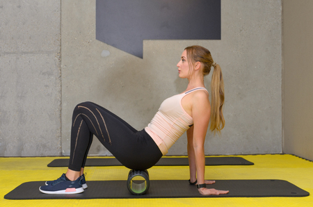 Young fit blonde woman exercising with foam roller at gym Foto de archivo