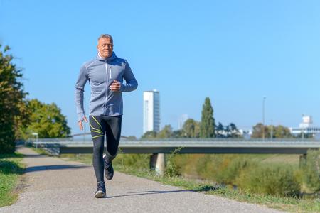 Middle-aged man jogging along alley in park on sunny day Reklamní fotografie