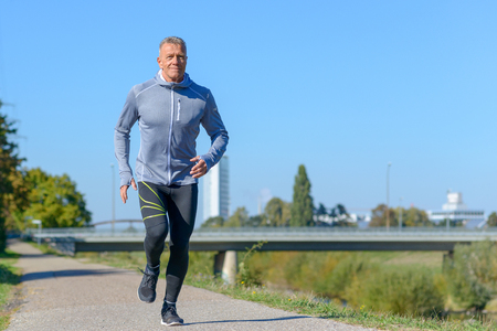 Front view of gray smiling man wearing sportswear running along river