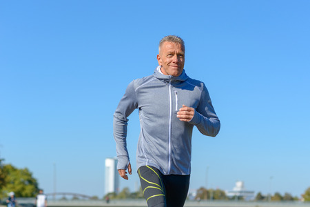 Front view of gray smiling man wearing sportswear running along river in a close up view Stock Photo