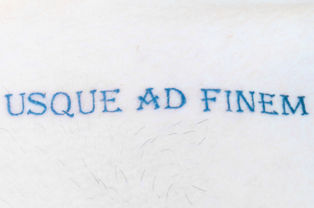 Usque ad Finem, a Latin phrase used in heraldry meaning To The Very End, or Fight Until You Die on Skin with copy space