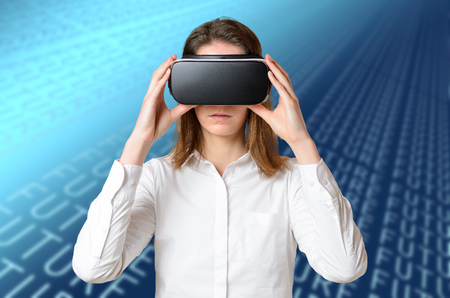 Young woman in white shirt adjusting 3D goggles on her head, holding black device with both hands, experiencing virtual reality. Half-length front portrait against blue abstract digital background