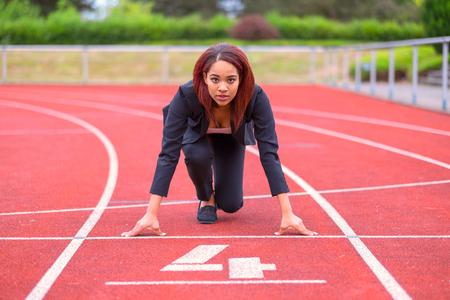 Konzeptbild einer Geschäftsfrau auf einer Rennstrecke in der Bereitschaftsposition an der Startlinie mit Blick auf die Kamera Standard-Bild