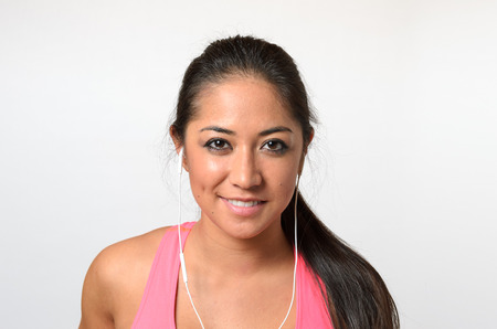Pretty young long-haired brunette woman in pink training top with earbuds, looking at camera and smiling. Close-up bust frontal portrait on white background Фото со стока
