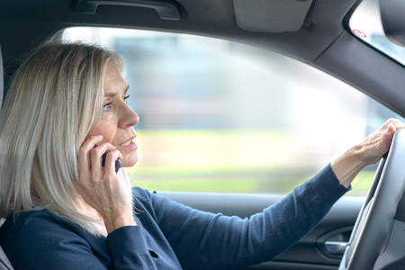 Mature woman driver chatting on her mobile in the car as she drives through town in a close up side view through the passenger window Imagens