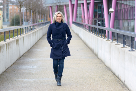 Trendy blond woman in a stylish blue outfit walking along a walkway in town approaching the camera with a friendly smile Stock fotó
