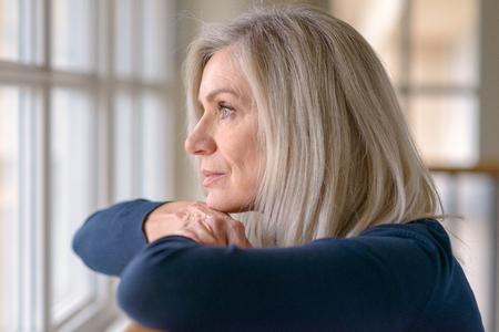Attraktive blonde Frau, die durch ein Fenster mit einem ernsten Gesichtsausdruck beobachtet, der ihr Kinn auf ihre Hände stützt, während sie sich auf ein Holzgeländer stützt